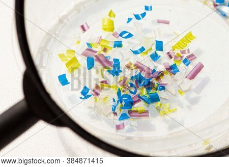 A Man Looking Through A Magnifying Glass. Water Pollution And Soil Microplastic. Macro Photo
