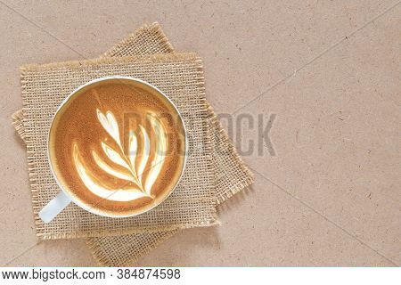 Latte Art On Cappuccino Coffee Cup With Sackcloth On Craft Board.