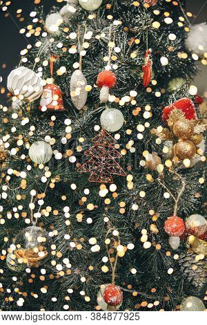 Christmas Tree Decoration Festive Background. Various Toys And Baubles And Holiday Lights On The Tre