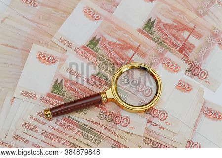 A Magnifying Glass With A Gold Handle Is Placed On Top Of Russian Banknotes Of Five Thousand Rubles