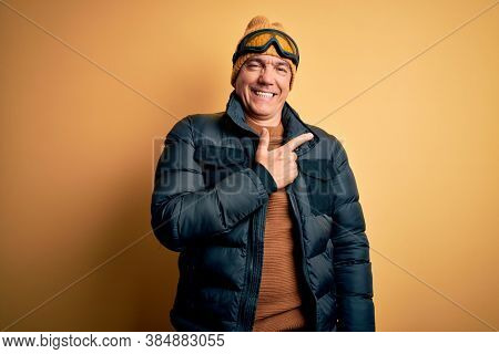 Middle age handsome grey-haired skier man on vacation wearing ski goggles cheerful with a smile of face pointing with hand and finger up to the side with happy and natural expression on face