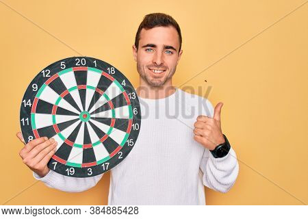 Young handsome man with blue eyes holding dartboard over isolated yellow background happy with big smile doing ok sign, thumb up with fingers, excellent sign