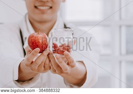 Asian Male Nutritionists Hold Red Apples And Supplementary Capsules That Is Extracted From Apples Wi