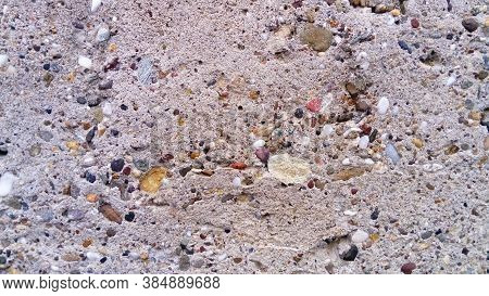Close-up Of Concrete Pavement With Built-in Elements. Stones Stick Out In Different Sizes And Colors