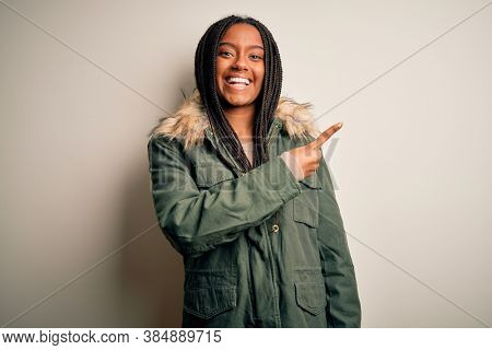 Young african american woman wearing winter parka coat over isolated background cheerful with a smile of face pointing with hand and finger up to the side with happy and natural expression on face