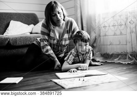 Woman reading a book with her little son on the floor in home. Black and white photo.