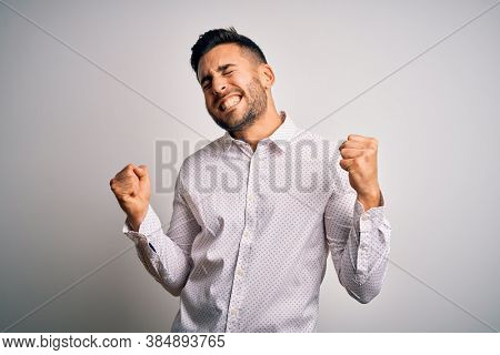 Young handsome man wearing elegant shirt standing over isolated white background very happy and excited doing winner gesture with arms raised, smiling and screaming for success. Celebration concept.