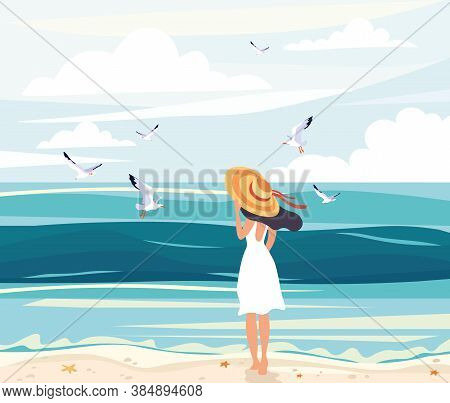 Woman In A Straw Sunhat At The Seaside Standing On The Beach Looking Out Over The Ocean Watching Sea