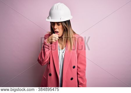 Young beautiful brunette architect woman wearing safety helmet over pink background feeling unwell and coughing as symptom for cold or bronchitis. Health care concept.
