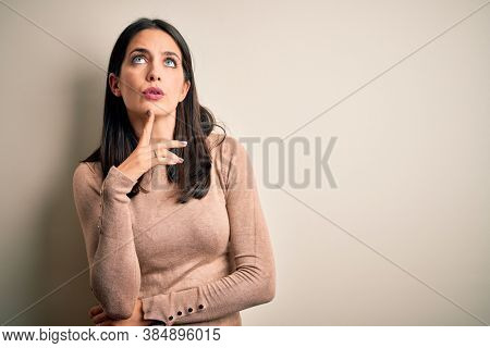 Young brunette woman with blue eyes wearing casual sweater over isolated white background Thinking concentrated about doubt with finger on chin and looking up wondering