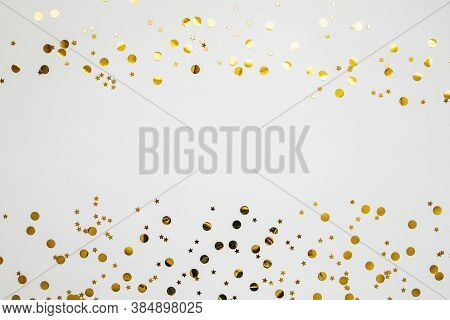 Gold And Silver Confetti On A White Festive Background. In The Middle There Is Space For Text Or Cop