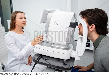 Eye Doctor Woman Is Doing A Diagnostic Vision Exam Adult Man. Concept Of Eye Care. Vision Correction
