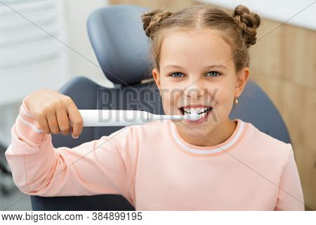 Pretty Little Girl Cleaning Teeth With Electric Sonic Toothbrush. Perfect Removing Plaque With A Mod