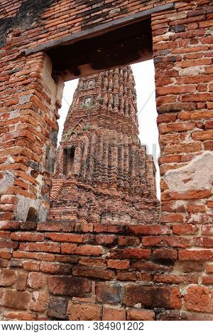 The Main Phra Prang Or Pagoda, The View Through The Window Of Church In The Ruins Of Ancient Remains