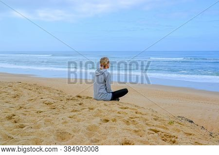 Peaceful Healthy And Fit Young Woman Meditating On The Beach. Woman Meditating In Lotus Pose.