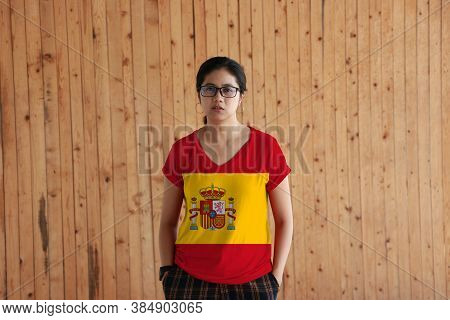 Woman Wearing Spain Flag Color Shirt And Standing With Two Hands In Pant Pockets On The Wooden Wall