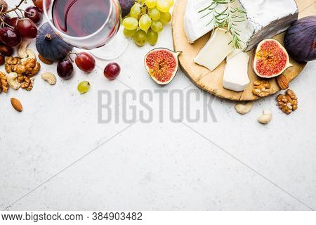 Camembert Or Brie Cheese With Fresh Figs, Honeycomb And Glass Of Wine On Serving Board Over White Ba