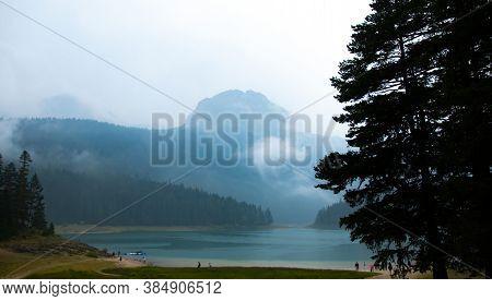 Black Lake In Front Of Zabljak Mountain In Fog In Montenegro, Tourism In Europe, Travel To Beautiful