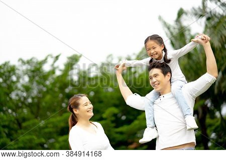 Happy Family: Mother, Father, Child Daughter At Park. Family Relaxing On Holiday.