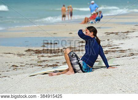 Holmes Beach, Anna Maria Island, Fl / Usa -  October 4, 2013: Surfer Resting On Anna Maria Island Wh
