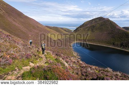 Back View Of A Teenage Girl And Adult Man Walking Down A Hiking Trail In The Quiraing On The Isle Of
