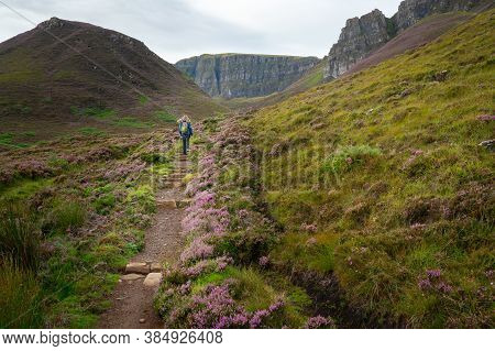 Back View Of A Teenage Girl Walking Up A Hiking Trail Towards The Quiraing Rocks On The Isle Of Skye