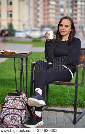 Beautiful Woman Drinking Coffee In A Cafe. Young Woman Sitting On A Chair, Holding A White Mug With