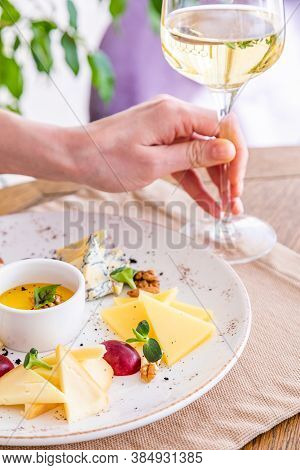 The Hand Takes A Glass Of White Wine. Cheese Platter. A Plate With A Variety Of Cheeses. Snacks. Gla