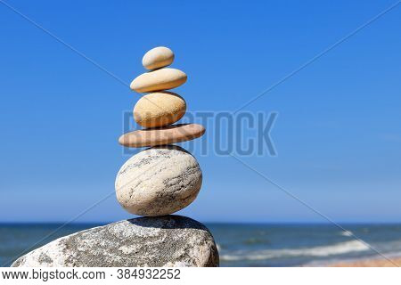 Rock Zen Pyramid Of Balanced Stones Against The Background Of The Sea And Blue Sky. Concept Of Balan