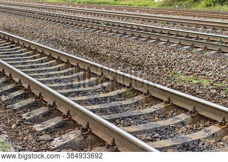 Railroad Tracks At Railway Station, Transportation. Empty Railroad Tracks. Perspective View.