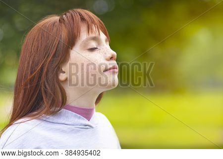 Young Red-haired Girl Inhales Air In The Park. Cute Little Girl Is Resting In Nature In The Fresh Ai