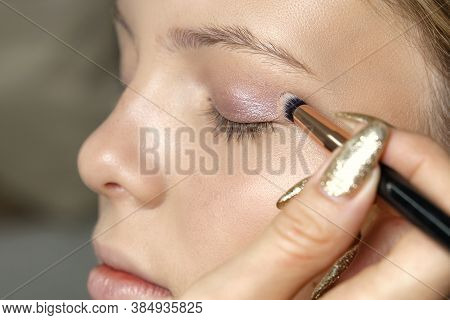 Professional Make-up Artist Makes Makeup With False Eyelashes To A Young Girl. Preparation Of The Mo