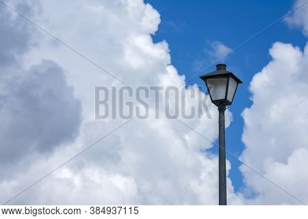 Horizontal Shot Of A Lamppost Against A Blue Cloudy Sky.
