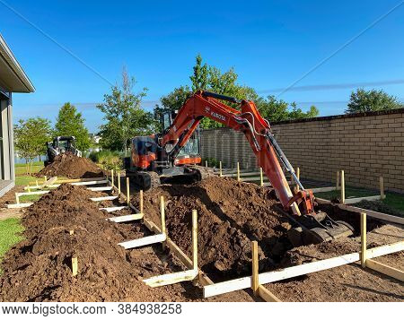 A Backhoe Digging A Hole For A Pool Behind A House In Orlando, Florida.