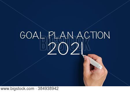 2021 Goal Plan Action. Man Writes On A Blue Background 2021 Goal Plan Action