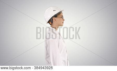 Scientist Physicist Woman Walking In Lab Coat And Hardhat On Gra