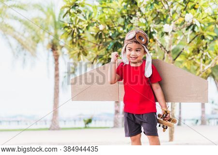 Happy Asian Funny Child Or Kid Little Boy Smile Wear Pilot Hat And Goggles Play Toy Cardboard Airpla