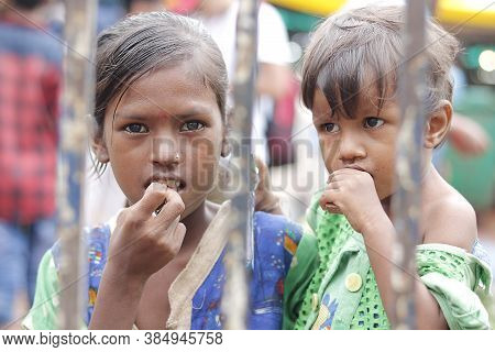 Ahemdabad, Gujarat, India - 20th June, 2019: Poor Indian Helpless Street Girl Holding Little Kid In