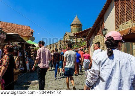 Mtskheta, Georgia - May 1, 2018: Tourists Walking On Street With Gift Souvenir Shops In The Historic
