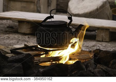 A Kettle, Blackened With Soot, Heating Over A Campfire Surrounded With Rocks.