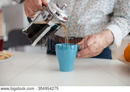 Senior Man Pouring Hot Coffee From French Press During Breakfat In Kitchen. Elderly Person In The Mo