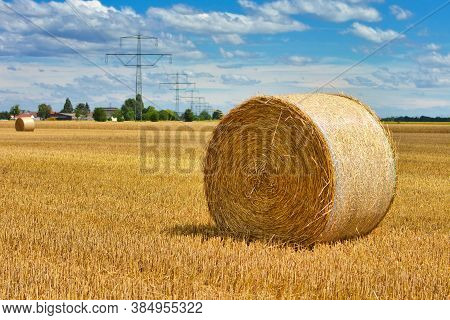 Large Round Hay Bale On Agricultural Field In Front Of Blue Sky