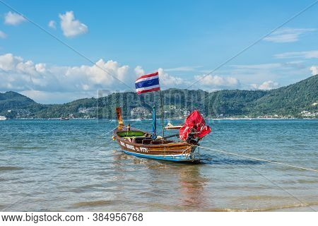 Phuket, Thailand - November 29, 2019: Traditional Longtail Boat With Thailand Flag On The Shore Of P