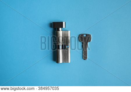 A Door Lock Cylinder Core With Key On The Blue Background. The Cylinder Of The Lock With Key. Instal