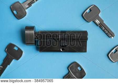 A Door Lock Cylinder Core With Keys On The Blue Background. The Cylinder Of The Lock With Keys. Inst