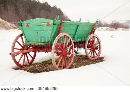 Old Wooden Cart. Green Cart Standing In The Snow