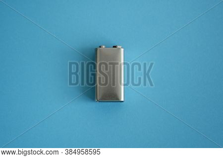 High Voltage Battery On A Blue Background. Silver Volt Battery. 9v Advanced Lithium Batteries.