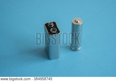 High Voltage Volt 9v Battery And Alkaline Aa Battery On A Blue Background. Energy.