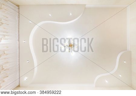 Stretch Ceiling White And Complex Shape With Halogen Spots Lamps And Drywall Construction In Empty R