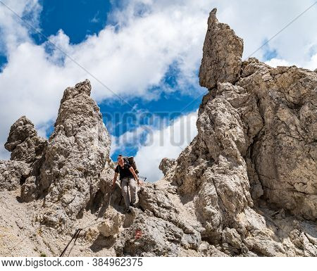 Young Woman Summer Hiker With Backpack Climbing With Help Of Metal Cables, Iron Rungs, Pegs, And Ste
